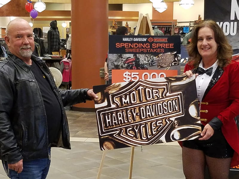People holding a Harley-Davidson sign