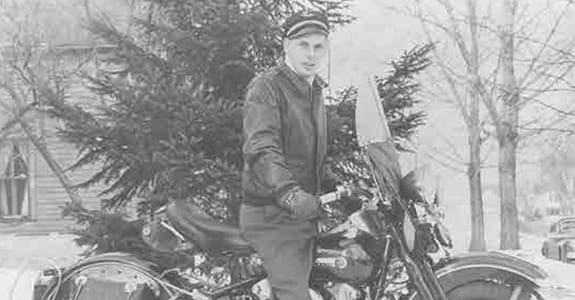 Black and white image of a guy on a motorcycle