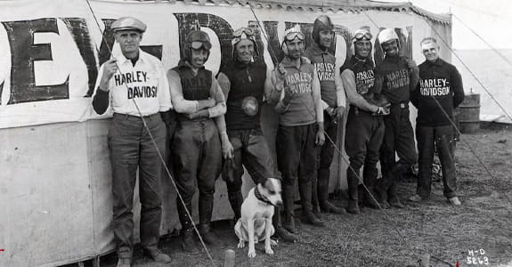 Black and white image of Harley Davidson riders and their dog