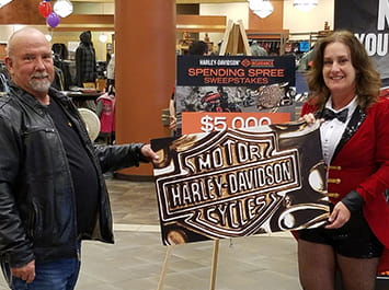 Man and lady standing in front of Harley Davidson sign