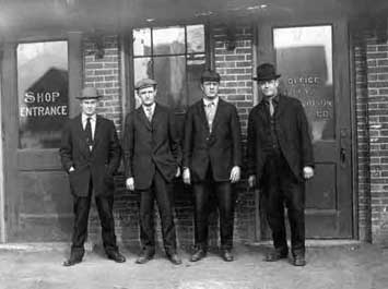 Old black and white photo of men standing in front of building