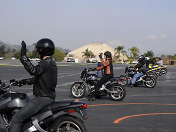 A row of people sitting on motorcycles