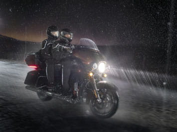 Two people riding a motorcycle in the dark and in the rain