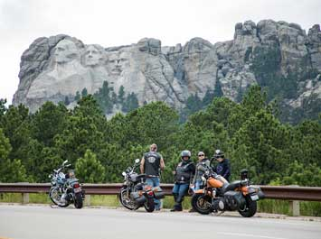Motorcycles parked on a road in front of Mount Rushmore