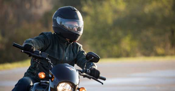 Someone riding a motorcycle wearing a black helmet