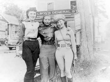 A black and white photo of three women standing and posing for a picture