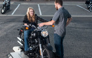 Woman on a motorcycle with male instructor