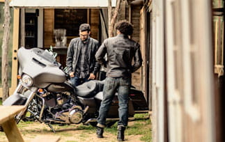 Two motorcycle riders looking at a bike